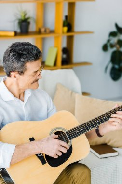 cheerful senior man playing acoustic guitar in living room