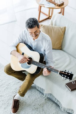 overhead view of cheerful senior man playing acoustic guitar in living room