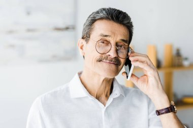 cheerful senior man in glasses talking on smartphone at home