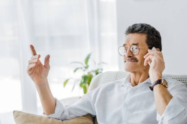 happy senior man with mustache talking on smartphone and pointing firh finger at home