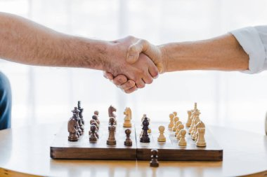cropped view of pensioners shaking hands after playing chess at home