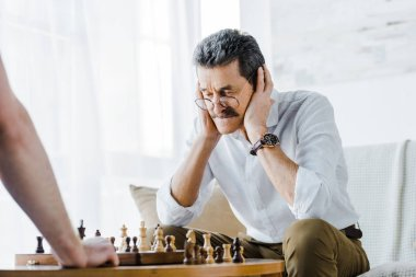 Selective focus of senior man with mustache covering ears while playing chess with friend at home stock vector