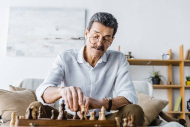 pensive senior man with mustache playing chess at home