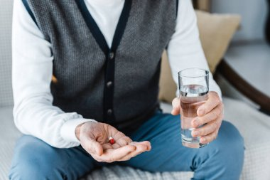 cropped view of retired man holding pill and glass of water at home