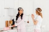 dívka, tleskání a blahopřání s úsměvem africké americké přítelkyni s mezinárodní Dámské day během pyžamový večírek