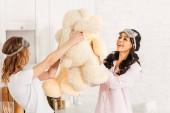 Fotografia belle ragazze multiculturale giocando con orsacchiotti durante il pigiama party a casa