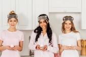 mnohonárodnostní krásky v spící masky drží košíčky a při pohledu na fotoaparát během pyžamový večírek