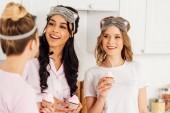 usmívající se mnohonárodnostní krásky v spící masky drží košíčky během pyžamový večírek