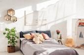 moderní design interiéru ložnice medvídek hračky, polštáře, rostliny a postel