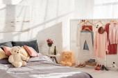 moderní design interiéru ložnice s Medvídek hračky, polštáře, šaty na regály a postel