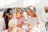 beautiful surprised multicultural girls in sleeping masks with champagne glasses using smartphone during pajama party
