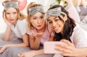 szép mosolygó multikulturális lányok alszik feküdt az ágyban, és figyelembe selfie smartphone alatt pizsama party maszkok