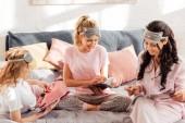 krásné usměvavé multikulturní dívky v spící masky čtení časopisů během Pyžama strana