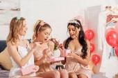szép, mosolygós multikulturális lányok hálóruhák megnyitása bemutatja alatt pizsama party