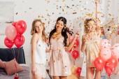krásné multikulturní dívky držení sklenky na sekt a slaví pod padající konfety během pyžamový večírek