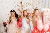Fotografie beautiful cheerful multicultural girls holding champagne glasses and celebrating under falling confetti during pajama party