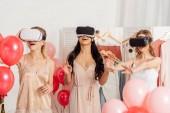 aufgeregte multiethnische Mädchen in Nachtwäsche und Vr-Headset mit Virtual-Reality-Erfahrung während Pyjama-Party