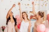 Fotografie multikulturelle Schönheiten mit Sektgläsern Toasten und unter fallenden Konfetti im Pyjama-Party feiern