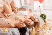 Fényképek szép boldog multikulturális lányok arany konfetti, ágyban fekve, és látszó-on fényképezőgép