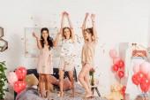 Fotografie krásné multikulturní dívky v noční tančí a baví pod padající konfety během pyžamový večírek
