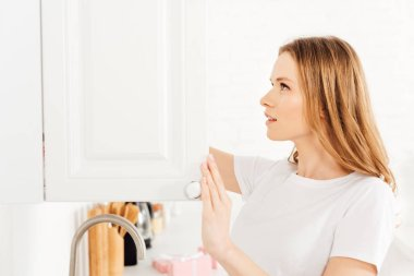 beautiful girl in pajamas opening cupboard in kitchen with copy space