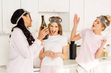 beautiful multicultural girls cheering and celebrating with champagne during pajama party