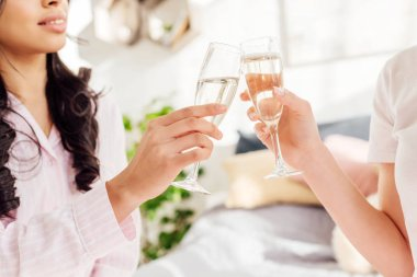 cropped view of multicultural girls clinking champagne glasses at home