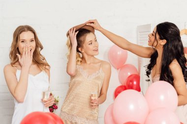 beautiful smiling multiethnic girls in nightwear celebrating with glasses of champagne and balloons during pajama party