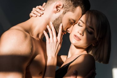passionate blonde woman and shirtless man embracing with shadows on bodies