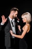 elegantní blondýna žena Svlékání pohledný muž izolované na černém pozadí
