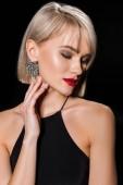 nádherné glamour žena náušnice a černých šatech, izolované na černém pozadí