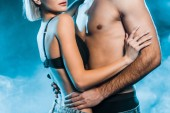 oříznutý pohled svůdné páru objímání na modrém kouřové pozadí