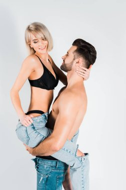 shirtless man holding smiling woman in underwear and jeans isolated on grey