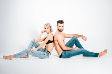 beautiful girlfriend and handsome boyfriend in underwear and jeans sitting back to back on grey
