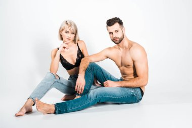 beautiful couple in underwear and jeans sitting on grey