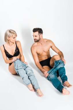 handsome bearded man and smiling young woman wearing jeans on grey
