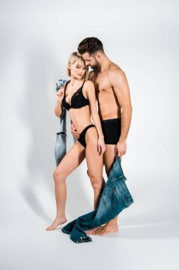 beautiful couple embracing in underwear and posing with jeans on grey