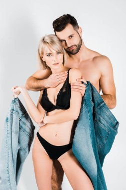 attractive sensual couple in underwear posing with jeans isolated on grey