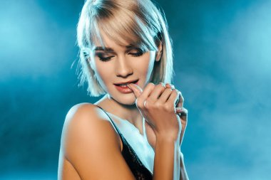 seductive blonde woman posing on blue smoky background