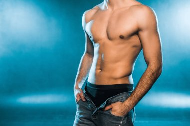 cropped view of shirtless muscular man in black underwear and jeans posing on blue smoky background