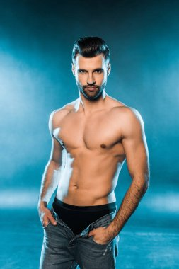 handsome muscular man in black underwear and jeans posing on blue smoky background
