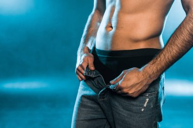 cropped view of sexy man in black underwear and jeans posing on blue smoky background