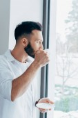 Vážný muž popíjel kávu a při pohledu na okna