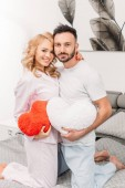 Fotografie Romantic couple embracing and holding toy hearts