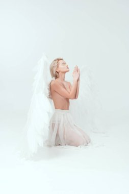 Beautiful woman with angel wings praying isolated on white stock vector