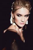 Fotografie portrét krásné ženy v zlaté doplňky představují izolované na černém pozadí