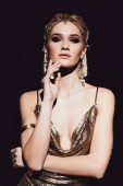 beautiful woman in golden accessories posing and looking at camera isolated on black
