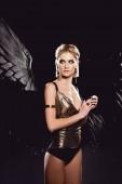 Fotografie schöne sexy Frau mit Engelsflügeln und goldenen Accessoires posiert isoliert auf schwarz