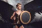 Fényképek szép szexi nő pózol, pajzs és kard, a fekete háttér harcos jelmez és angel szárnyak