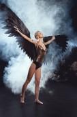 Krásná sexy žena s černým andělská křídla a natažených rukou pózuje na černém pozadí